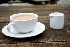Copo do café da manhã com leite na tabela de madeira marrom exterior Fotos de Stock Royalty Free