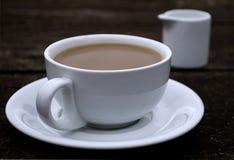 Copo do café da manhã com leite na tabela de madeira marrom exterior Imagem de Stock