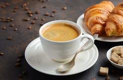 Copo do café fresco com os croissant no fundo escuro fotografia de stock royalty free