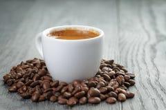 Copo do café fresco com os feijões de café no carvalho Imagens de Stock