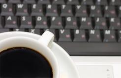 Copo do café no portátil imagem de stock