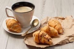 Copo do café preto com os croissant frescos no papel de envolvimento Fotos de Stock Royalty Free