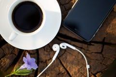 Copo do café preto e do telefone esperto no fundo de madeira Foto de Stock Royalty Free