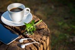 Copo do café preto e do telefone esperto no fundo de madeira Imagens de Stock Royalty Free