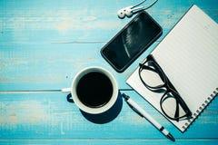 Copo do café preto e do telefone esperto com materiais de escritório; vidros da pena, do caderno e dos olhos no fundo de madeira  foto de stock