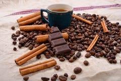 Copo do café quente com varas de canela, barra de chocolate mordida Foto de Stock