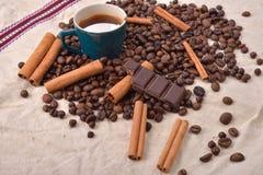 Copo do café quente com varas de canela, barra de chocolate mordida Fotos de Stock Royalty Free