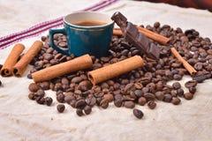 Copo do café quente com varas de canela, barra de chocolate mordida Fotos de Stock