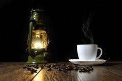 Copo do café quente, de grões dispersadas e de lâmpada Foto de Stock
