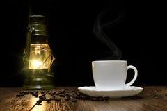 Copo do café quente, de grões dispersadas e de lâmpada Imagens de Stock