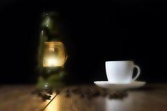 Copo do café quente, de grões dispersadas e de lâmpada - blured Fotos de Stock Royalty Free