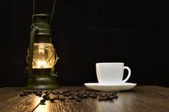 Copo do café quente, de grões dispersadas e de lâmpada - blured Foto de Stock