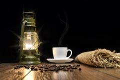 Copo do café quente, de grões dispersadas e de lâmpada de querosene Imagens de Stock Royalty Free