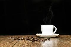 Copo do café quente e de grões dispersadas na tabela Foto de Stock