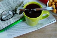 Copo do café quente em um bom dia e em um jornal de manhã Fotografia de Stock