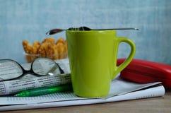 Copo do café quente em um bom dia e em um jornal de manhã Foto de Stock