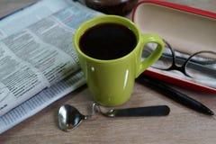 Copo do café quente em um bom dia e em um jornal de manhã Fotografia de Stock Royalty Free