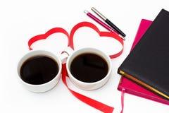 Copo do café preto, de um coração da fita vermelha, de diários e de penas em um fundo branco Vista superior Imagens de Stock Royalty Free