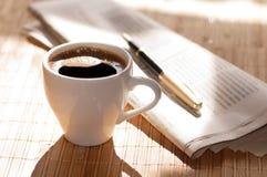 Copo do café preto, do jornal e de uma pena contra Imagens de Stock
