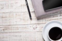 Copo do café preto e do livro de nota quentes, pena na tabela de madeira Imagem de Stock Royalty Free