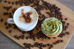 Copo do cappuccino com os feijões do queque e de café Foto de Stock Royalty Free