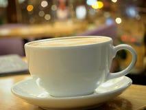 Copo do cappuccino contra o fundo das luzes Imagens de Stock