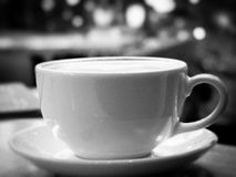 Copo do cappuccino contra o fundo das luzes Imagens de Stock Royalty Free
