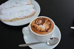 Copo do cappuccino e do bolo quentes Imagens de Stock