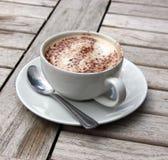 Copo do Cappuccino na tabela de madeira do slat Foto de Stock