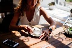 Copo do cappuccino nas mãos foto de stock