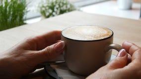 Copo do cappuccino quente com espuma, que é tocada por uma mulher com mãos bem arrumados bonitas em um café à moda vídeos de arquivo