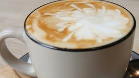 Copo do cappuccino quente, fresco em uns pires em um fim da tabela acima da vista filme