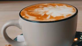 Copo do cappuccino quente, fresco em uns pires em um fim da tabela acima da vista vídeos de arquivo