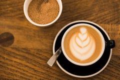 Copo do cappucino quente em um copo do blak com arte do café no fundo de madeira da tabela estilo do hippster foto de stock royalty free