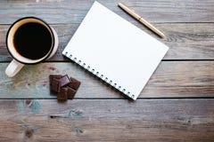 Copo do chá, do chocolate e de um caderno em uma tabela de madeira, espaço da cópia fotos de stock