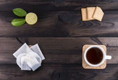 Copo do chá com cookies, cal e saquinhos de chá do chá na tabela de madeira Foto de Stock
