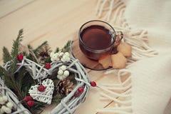 Copo do chá com estrelas das cookies com um coração da grinalda do Natal de w fotografia de stock