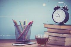 Copo do chá com livros e pulso de disparo no fundo de madeira foto de stock