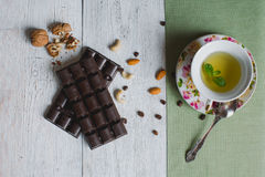 Copo do chá com na barra de chocolate velha de linho f da tabela da hortelã Foto de Stock