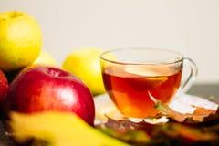 Copo do chá com o limão ao lado das maçãs maduras fotografia de stock royalty free