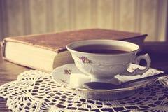 Copo do chá com o livro no efeito do vintage do guardanapo fotografia de stock