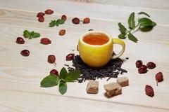 Copo do chá com rosas ancas, na tabela de madeira Um copo feito do limão real Imagens de Stock Royalty Free
