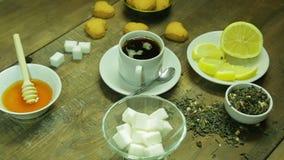 Copo do chá, da soldadura, do mel e do limão em uma tabela de madeira O plano médio filme