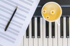 Copo do chá de camomila em um piano, em uma folha de música e em uma pena Vista superior, fim acima Ainda vida, conceito fotos de stock royalty free