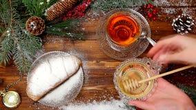 Copo do chá A do inverno do chá com mel e croissant ou cookies, um ramo de uma árvore de Natal na neve, luzes de Natal filme