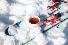 Copo do chá na neve e no esqui foto de stock royalty free