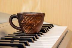 Copo do chá nas chaves do piano, ruptura durante o lessons_ da música imagem de stock