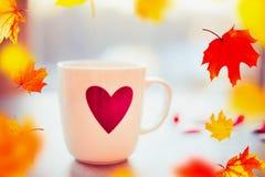 Copo do chá ou do café na janela ainda com as folhas de queda do outono, vista dianteira Imagens de Stock Royalty Free