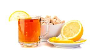 Copo do chá preto com limão, limão em uns pires, açúcar mascavado fotografia de stock royalty free