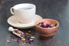 Copo do chá preto com pétalas e ervas imagem de stock
